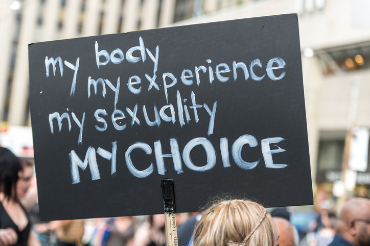 """Toronto, Canada - May 25, 2012: A protest sign during """"Slut Walk 2012"""", a protest event about sexual assault and victims' rights, among other related issues."""